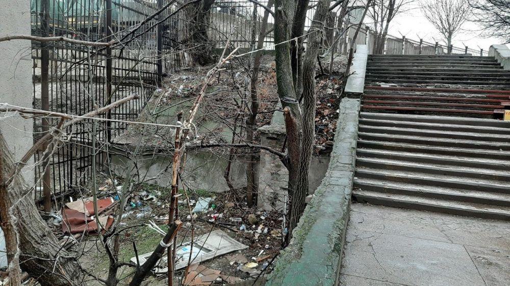 Симферопольские дворники убирают замусоренную лестницу, ведущую к радиорынку