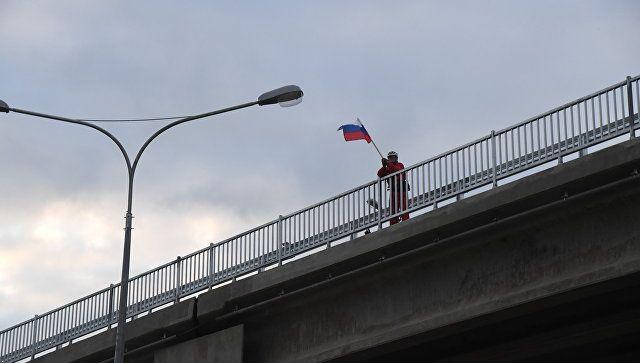 Мужчина с флагом России приветствует первых участников движения по Крымскому мосту. 16 мая 2018