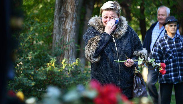 Люди несут цветы к народному мемориалу в Керчи в память о погибших в Керченском политехническом колледже, в котором произошли взрыв и стрельба