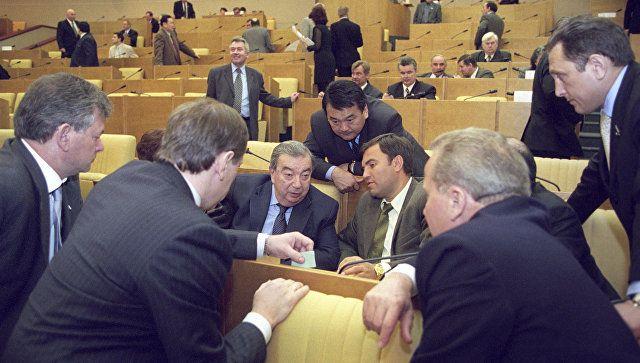 Депутат Евгений Примаков (на среднем плане слева) среди коллег в зале заседаний Государственной Думы Российской Федерации.