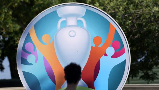 Мужчина проходит мимо вывески, рекламирующей предстоящий чемпионат Европы по футболу 2020 года в Баку, Азербайджан. 10 июня 2021 года